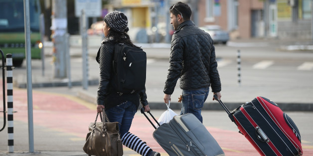 SOFIA, BULGARIA - DECEMBER 07:  A young Roma couple walk with suitcases outside the main bus station on December 7, 2013 in Sofia, Bulgaria. Restrictions on the freedom of Bulgarians and Romanians to work in the European Union are due to run out by December 31, though several EU leaders, including British Prime Minister David Cameron, are considering imposing temporary restrictions to cut the flow of Romanians and Bulgarians arriving in EU countries. Many EU nations have voiced concern over too