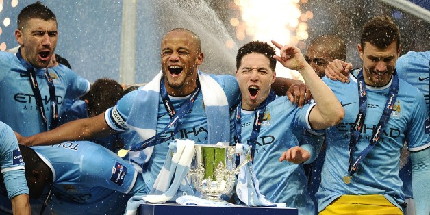Manchester City's Vincent Kompany (centre) and Samir Nasri (second right) celebrate as they prepare to lift the Capital One Cup trophy following victory over Sunderland