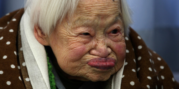 OSAKA, JAPAN - MARCH 05:  Misao Okawa, who is recognised by Guinness World Records as the world's oldest woman, reacts during her 115th birthday celebrations at Kurenai Nursing Home on March 5, 2013 in Osaka, Japan. Misao Okawa, was born in Tenma, Osaka, on March 5, 1898. A descendent of Kimono merchants, she married in 1919 and had three children, of which a daughter and a son are still alive, and four grandchildren and six great-grandchildren.  (Photo by Buddhika Weerasinghe/Getty Images)