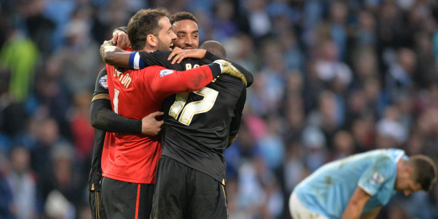 Wigan Athletic's English goalkeeper Scott Carson (L) joins his teammates in celebrating at the final whistle during the English FA Cup quarter-final football match between Manchester City and Wigan Athletic at the Etihad Stadium in Manchester, northwest England, on March 9, 2014. Wigan won 2-1.   AFP PHOTO / PAUL ELLISRESTRICTED TO EDITORIAL USE. No use with unauthorized audio, video, data, fixture lists, club/league logos or 'live' services. Online in-match use limited to 45 images, no video em