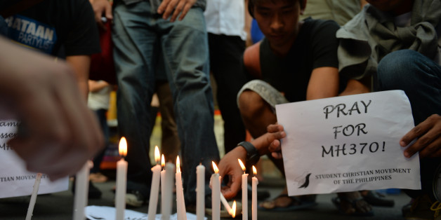 Students light candles as they hold placards in solidarity with families of the passengers of the missing Malaysia Airlines flight MH370 plane during a candle light vigil at the university belt in Manila on March 13, 2014. Malaysia said on March 13 that satellite images of suspected debris from a missing jet were yet another false lead, and debunked a report the plane had flown on for hours after losing contact -- leaving the nearly week-old mystery no closer to being solved. AFP PHOTO/TED ALJIBE        (Photo credit should read TED ALJIBE/AFP/Getty Images)