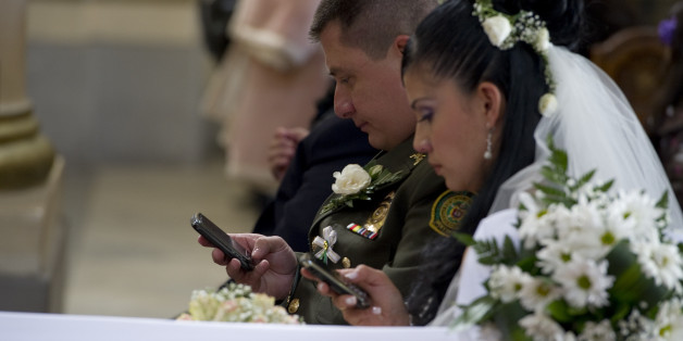 A bride and groom use their mobile phones during a mass wedding of police officers at the Cathedral of Bogota, on December 9, 2011. Ninety-six couples are getting married in the same ceremony.  AFP PHOTO/Luis ACOSTA (Photo credit should read LUIS ACOSTA/AFP/Getty Images)