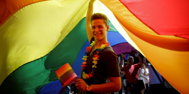PRAGUE, CZECH REPUBLIC - AUGUST 17:  A participant holds up a large rainbow flag during the third Prague Pride March on August 17, 2013 in Prague, Czech Republic. Several thousand people marched through city centre in support of Lesbian, Gay, Bisexual and Transgenders (LGBT) rights.  (Photo by Matej Divizna/Getty Images)