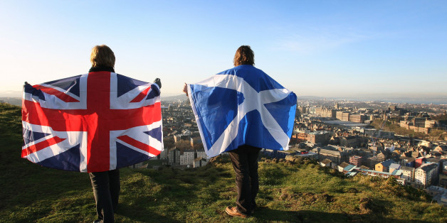Scottish and English flags held up over Edinburgh, Scotland