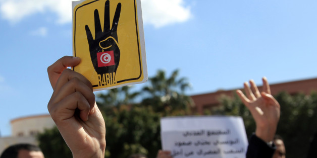 Tunisians flash 'Rabia' sign as they gather outside the Egyptian embassy in Tunis to protest the Egyptian judge's decision on Tuesday to sentence 528 supporters of the Muslim Brotherhood to death on March 28, 2014. (Photo by Yassine Gaidi/Anadolu Agency/Getty Images)