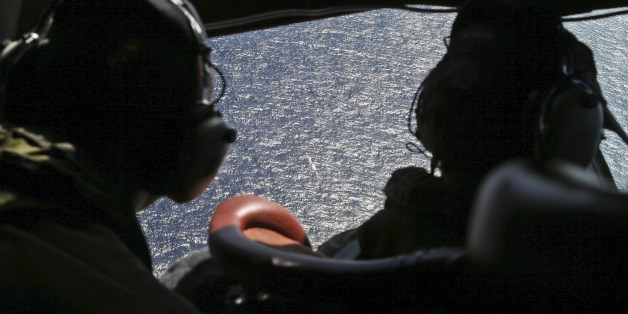 Crew member look out the cockpit windows of a RNZAF P3 Orion during search operations for wreckage and debris of missing Malaysia Airlines Flight MH370 in the Southern Indian Ocean, near the coast of Western Australia on April 4, 2014.  A US Navy 'black box' detector made its much-anticipated debut in the oceanic hunt for flight MH370 on April 4 but Australia's search chief warned it was crunch time with the box's signal set to expire soon. AFP Photo/Nick Perry/Pool        (Photo credit should r