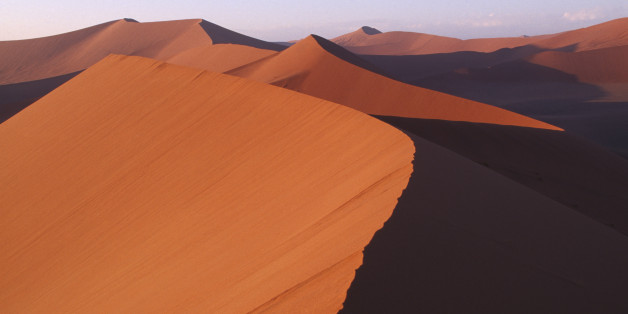 NAMIBIA Namib Desert Red sand dunes partially cast in shadow