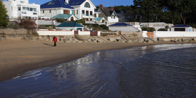 People walk on the beach in the exclusive residential area of Sandbanks on in Poole, England