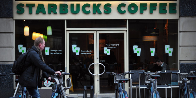 TO GO WITH AFP STORY BY RUTH HOLMES A man parks his hire bicycle outside a branch of Starbucks in central London on February 1, 2013. Despite pledging to pay millions of pounds in extra tax in Britain, Starbucks faces a battle to restore its reputation over its fiscal stance, with analysts saying the offer is 'too little too late'. AFP PHOTO / CARL COURT        (Photo credit should read CARL COURT/AFP/Getty Images)