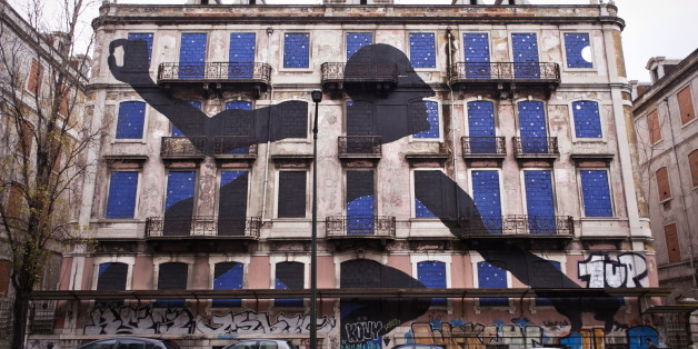A giant man is sticking out his head and arms of the windows of an old abandoned building. The art piece is made by street artist Sam3 who is one out of 16 artists who took part in the Crono Project in Lisbon. Portugal 2013. (Photo by: PYMCA/UIG via Getty Images)