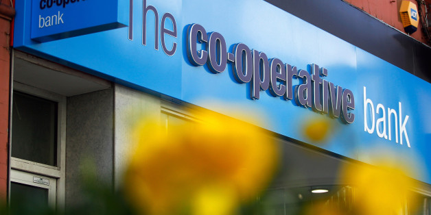 A sign sits above the entrance to a Co-Operative Bank Plc bank branch in Altrincham, U.K., on Tuesday, March 11, 2014. Co-Operative Group Ltd. Chief Executive Officer Euan Sutherland offered to resign after he publicly complained that a board member may have leaked details about his pay, according to a person with knowledge of the matter. The Co-Op Group were forced in October 2013 to give up control of Co-Operative Bank Plc to help plug a 1.5 billion pound capital hole at the division. Photogra