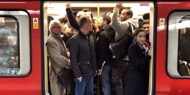 Passengers squeeze on to a busy tube train during strike, at kings cross station.