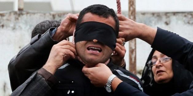 교수대에 오른 살인범 발랄의 목에 쓰인 올가미를 피해자 어머니가 풀어주고 있다.