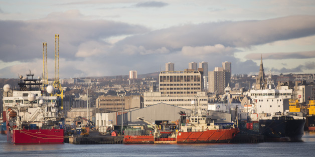 Vessels sit docked at Aberdeen Harbour, operated by the Aberdeen Harbour Board, as the city skyline is seen beyond in Aberdeen, U.K., on Thursday, Dec. 12, 2013. A report showed U.K. exports fell 1.3 percent in October from the previous month, while imports dropped 1.9 percent. Photographer: Simon Dawson/Bloomberg via Getty Images