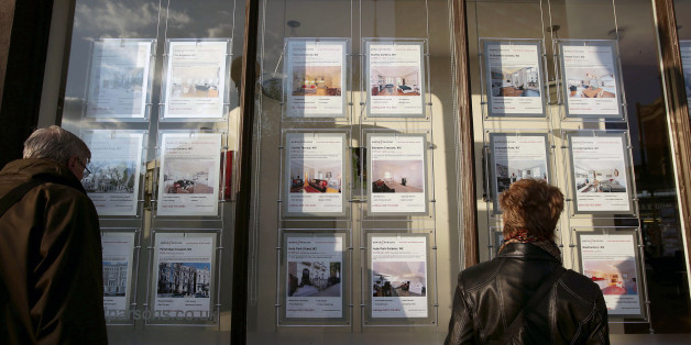 People looking art property signs displayed in the window of Marsh & Parsons estate agents in Notting Hill, London.