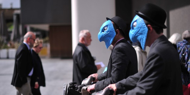 Protesters wearing masks in a satirical rendering of the eagle emblem of Barclay's Bank stage a demonstration near the venue of the Bank's annual general meeting in London on April 24, 2014.  Barclays announced, amid rising anger over its plans to pay higher bonuses, and as shareholders gathered for the bank's annual general meeting, that its first quarter profits will show a 'small reduction' from a year earlier after a fall in revenues at part of its investment bank. AFP PHOTO / CARL COURT