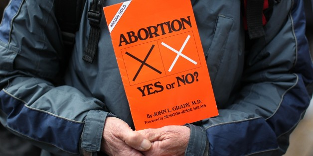 A anti abortion protestors holds up placards outside the Marie Stopes clinic, the first private clinic to offer abortions to women in Belfast, Northern Ireland on October 18, 2012. Dozens of pro-life campaigners protested outside the first abortion clinic in Northern Ireland as it opened to the public. Around 50 protesters brandishing placards saying 'Life is precious' and showing photographs of foetuses gathered outside the privately run clinic in an anonymous building in Belfast. AFP PHOTO/ Pe