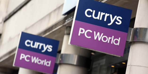 Signs hang above the entrance to a Currys PC World store, operated by Dixons Retail Plc, in London, U.K., on Thursday, March 20, 2014. Dixons Retail, the largest U.K. consumer-electronics retailer, said it's in talks to merge with Carphone Warehouse Group Plc, bringing together companies with combined revenue of about 12 billion pounds ($20 billion). Photographer: Chris Ratcliffe/Bloomberg via Getty Images
