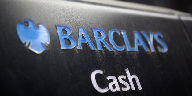 A Barclays logo sits above the word 'Cash' on an automated teller machine (ATM) outside a Barclays Plc bank branch in London, U.K., on Wednesday, May 7, 2014. Barclays will cut 7,000 jobs at its investment bank, bringing the total number of jobs to be cut across the firm by 2016 to 19,000, including the 12,000 the lender announced in February it would cut this year, Barclays said in a statement.  Photographer: Simon Dawson/Bloomberg via Getty Images