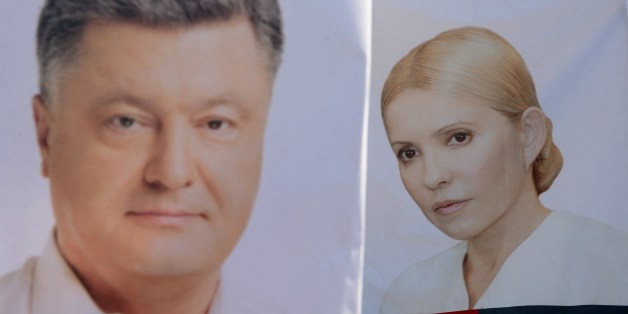 Placards depecting presidential candidates Yulia Tymoshenko (R) and Petro Poroshenko (L) are pictured in the western Ukrainian city of Lviv on May 21, 2014. Ukraine's glamorous but polarising ex-premier Yulia Tymoshenko was triumphantly released from prison during the pro-Western uprising in Kiev but is now a longshot in Sunday's presidential ballot due to mistrust of the corruption-stained old guard. AFP PHOTO/ YURKO DYACHYSHYN        (Photo credit should read YURIY DYACHYSHYN/AFP/Getty Images)