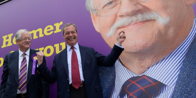 Leader of the UK Independence Party (UKIP) Nigel Farage (R) poses in front of a campaign poster for local UKIP candidate Roger Helmer (L) during his visit to Southwell, Newark upon Trent, central England on May 31, 2014.  The visit by Farage was part of UKIP campaigning ahead of the upcoming by-election in the town.     AFP PHOTO/ANDREW YATES        (Photo credit should read ANDREW YATES/AFP/Getty Images)