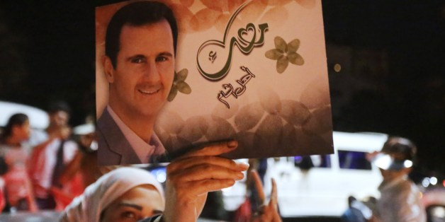 A woman holds a picture of re-elected Syrian President Bashar al-Assad as she celebrates in Damascus after he was announced as the winner of the country's presidential elections on June 4, 2014. Assad has been re-elected Syria's president with 88.7 percent of the vote after a poll labelled a farce by rebels fighting to overthrow him, whose outcome was never in doubt. AFP PHOTO/JOSEPH EID        (Photo credit should read JOSEPH EID/AFP/Getty Images)