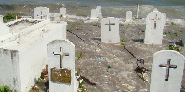 Marshalls-environment-climate-warming, by Giff JohnsonPicture taken in December 2008 shows a cemetery on the shoreline in Majuro Atoll being flooded from high tides and ocean surges. The low-lying Marshall Islands, a Pacific atoll chain that rises barely a metre above sea level, has announced plans for a wall to hold back rising sea levels.  AFP PHOTO         (Photo credit should read GIFF JOHNSON/AFP/Getty Images)