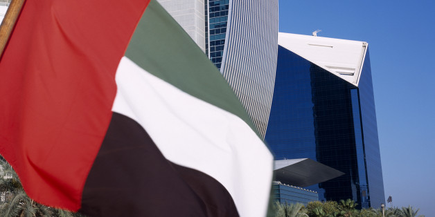 UAE, Dubai, national bank of Dubai seen from dhow on Dubai creek with UAE flag in the foreground.