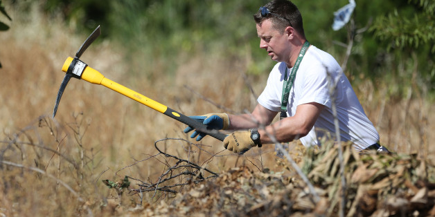 A British police officer clears an area of wasteland during the search for evidence of Madeleine McCann, in the town of Praia da Luz in Portugal where she went missing seven years ago.