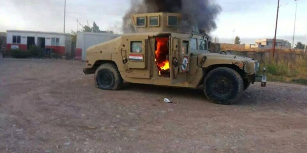 A picture taken with a mobile phone shows an armoured vehicle belonging to Iraqi security forces in flames on June 10, 2014,  after hundreds of militants from the Islamic State of Iraq and the Levant (ISIL) launched a major assault on the security forces in Mosul, some 370 kms north from the Iraqi capital Baghdad. Some 500,000 Iraqis have fled their homes in Iraq's second city Mosul after Jihadist militants took control, fearing increased violence, the International Organization for Migration sa