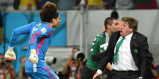Mexico's goalkeeper Guillermo Ochoa (L) and Mexico's coach Miguel Herrera (R) celebrate a goal by their team during a Group A football match between Croatia and Mexico at the Pernambuco Arena in Recife during the 2014 FIFA World Cup on June 23, 2014.  AFP PHOTO / DIMITAR DILKOFF        (Photo credit should read DIMITAR DILKOFF/AFP/Getty Images)