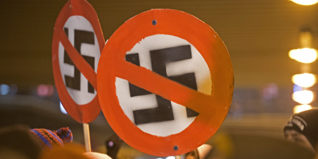 Left-wing demonstrators hold a sign with a crossed out swastika to protest against a far-right march marking the 67th anniversary of the allied bombings during World War II in Dresden, eastern Germany, on February 13, 2013. A massive bombing raid by Allied forces on Dresden beginning on February 13, 1945 sparked a firestorm that destroyed much of the historical centre of the city. AFP PHOTO / ROBERT MICHAEL        (Photo credit should read ROBERT MICHAEL/AFP/Getty Images)