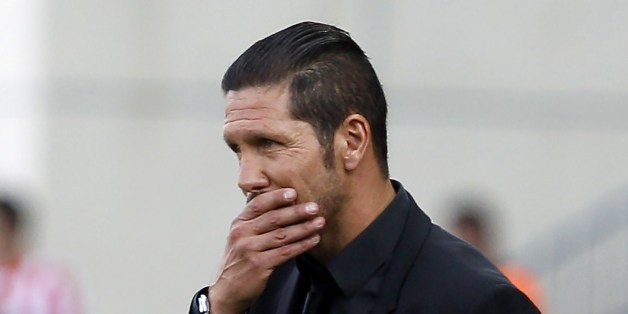 Atletico Madrid's Argentinian coach Diego Simeone reacts during the Spanish league football match Club Atletico de Madrid vs Malaga CF at the Vicente Calderon stadium in Madrid on May 11, 2014.   AFP PHOTO/ ALBERTO DI LOLLI        (Photo credit should read ALBERTO DI LOLLI/AFP/Getty Images)