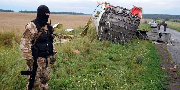An armed pro-Russia militant stands guard at the site of the crash of a Malaysian airliner carrying 298 people from Amsterdam to Kuala Lumpur in Grabove, in rebel-held east Ukraine, on July 18, 2014. Pro-Russian separatists in the region and officials in Kiev blamed each other for the crash, after the plane was apparently hit by a surface-to-air missile. Members of the UN Security Council demanded a full, independent investigation into the apparent shooting down of a Malaysia Airlines jet over U