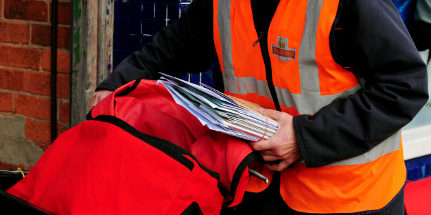 File photo dated 23/10/09 of a postal worker delivering mail in Beeston, Nottingham. Royal Mail has called for a review of the direct delivery market amid the fresh warnings it poses to the universal delivery market.