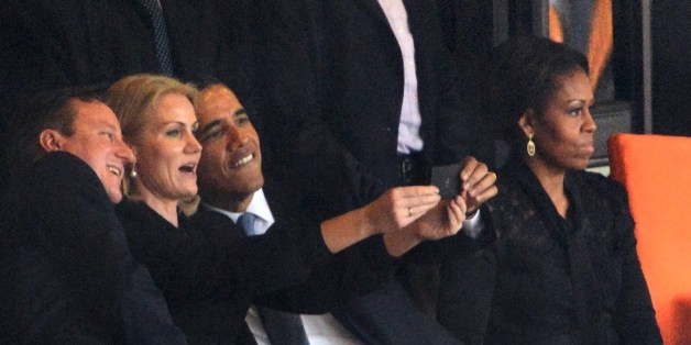-- AFP PICTURES OF THE YEAR 2013 --US President  Barack Obama (R) and British Prime Minister David Cameron pose for a selfie picture with Denmark's Prime Minister Helle Thorning Schmidt (C) next to US First Lady Michelle Obama (R) during the memorial service of South African former president Nelson Mandela at the FNB Stadium (Soccer City) in Johannesburg on December 10, 2013. Mandela, the revered icon of the anti-apartheid struggle in South Africa and one of the towering political figures of the