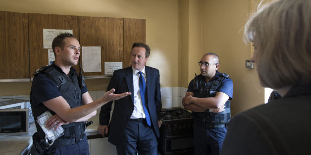 Prime Minster David Cameron (second left) and Home Secretary Theresa May (right) speak to Home Office Immigration Enforcement officers at a property where six immigrants were arrested in Slough, Berkshire.