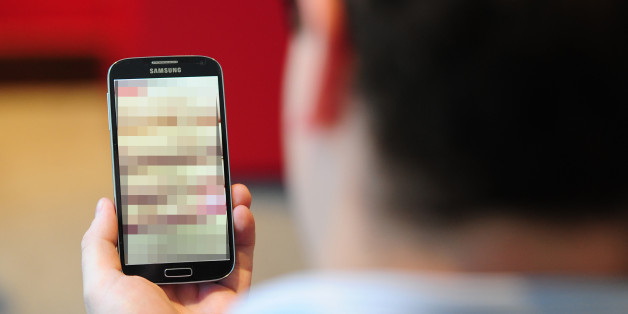"PICTURE POSED BY MODELUndated photo of a man looking at a mobile phone. Clarification is needed on the law around ""revenge porn"" and when it could lead to a prosecution, a committee of peers has said."