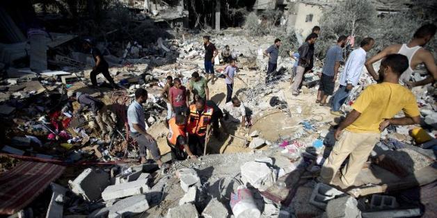 Des secouristes font des recherches dans les débris d'une maison visée par des frappes israéliennes dans le centre de la bande de Gaza le 3 août 2014