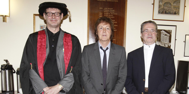 Sir Paul McCartney, co-founder of LIPA, presents an award to music producer Alan Moulder (left). He is one of seven luminaries from the arts and entertainment industry who were made Companions of the Liverpool Institute for Performing Arts, at the Institute's annual graduation ceremony.