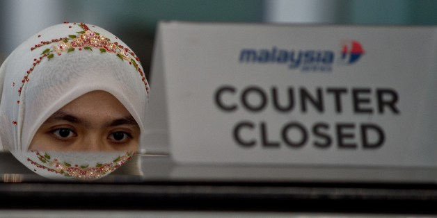 A Malaysia Airlines employee sits behind a closed ticket counter at the Kuala Lumpur International Airport in Sepang on July 20, 2014. Malaysia Airlines said it would offer full refunds to customers who want to cancel their tickets in the wake of the MH17 disaster, just months after the carrier suffered another blow when flight MH370 dissapeared.  AFP PHOTO/ MANAN VATSYAYANA        (Photo credit should read MANAN VATSYAYANA/AFP/Getty Images)
