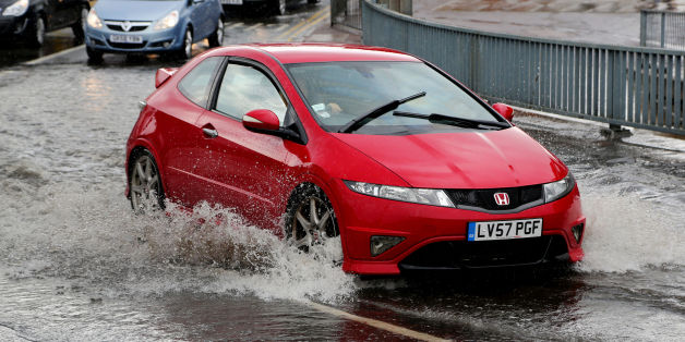 Cars pass through a flash flood following a heavy rain shower in Maidstone, Kent.