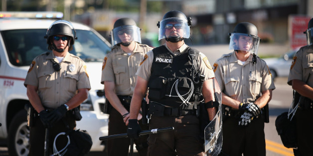 FERGUSON, MO - AUGUST 13: Police watch over demonstrators protest the shooting death of teenager Michael Brown on August 13, 2014 in Ferguson, Missouri. Brown was shot and killed by a Ferguson police officer on Saturday. Ferguson, a St. Louis suburb, has experienced three days of violent protests since the killing.  (Photo by Scott Olson/Getty Images)