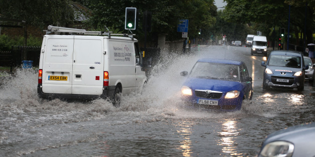 Traffic drives through a flooded road in Lewisham in south east London as a third of a month's rain could fall in just a few hours today as torrential downpours and thunderstorms hit parts of the UK.