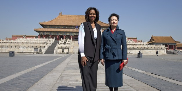 US First Lady Michelle Obama (L) and Peng Liyuan, wife of Chinese President Xi Jinping pose for photographers as they visit the Forbidden City in Beijing on March 21, 2014.  Michelle Obama arrived in Beijing with her mother and daughters to kick off a seven-day, three-city tour where she will focus on education and cultural exchange.    AFP PHOTO / POOL        (Photo credit should read ANDY WONG/AFP/Getty Images)