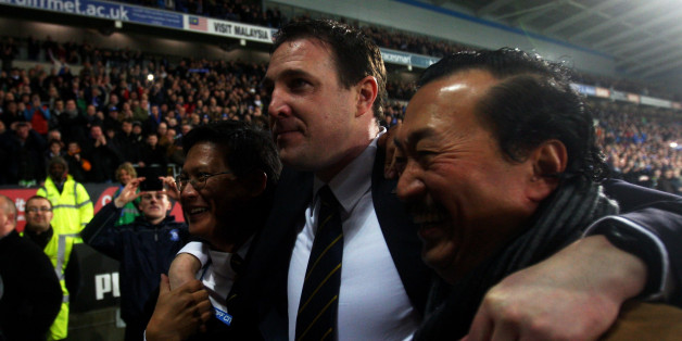 CARDIFF, WALES - JANUARY 24:  Malky Mackay the Cardiff City manager celebrates with club owner Tan Sri Vincent Tan Chee Yioun (right) and chairman Chan Tien Ghee (left) following his team's 3-1 victory in the penalty shootout during the Carling Cup Semi Final second leg match between Cardiff City and Crystal Palace at Cardiff City Stadium on January 24, 2012 in Cardiff, Wales.  (Photo by Michael Steele/Getty Images)
