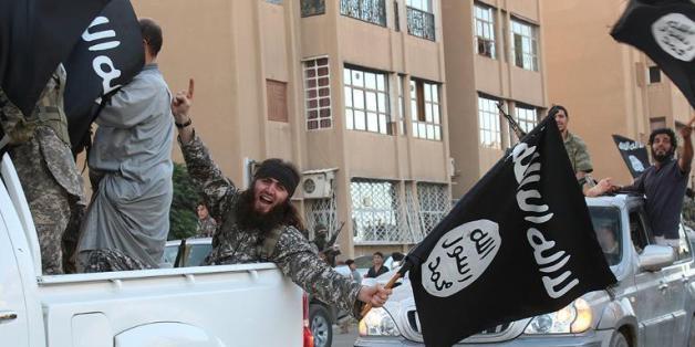 mage extraite du média jihadiste Al-Baraka news, le 11 juin 2014, montrant des militants de l'EI et leur drapeau noir dans la ville syrienne de Raga