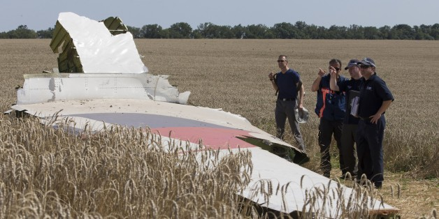 Australian and Dutch investigators examine a piece of the Malaysia Airlines Flight 17 plane, near the village of Hrabove, Donetsk region, eastern Ukraine Friday, Aug. 1, 2014. The investigators from the Netherlands and Australia plus officials with the Organization for Security and Cooperation in Europe traveled from the rebel-held city of Donetsk in 15 cars and a bus to the crash site outside the village of Hrabove. Then they started setting up a base to work from at a chicken farm. The investi
