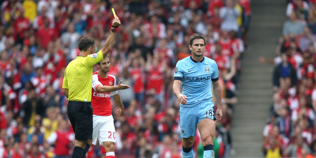 Referee Mark Clattenburg (left) shows the yellow card to Manchester City's Frank Lampard (right)