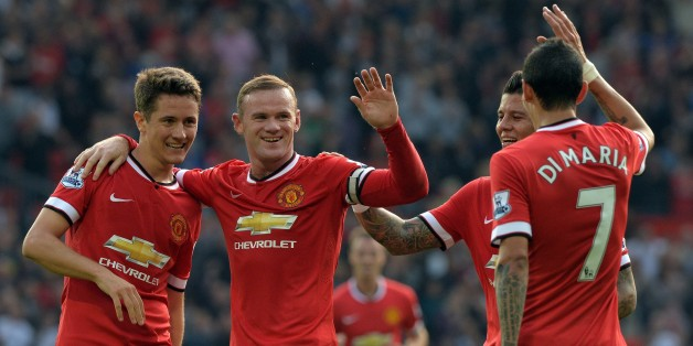 Manchester United's English striker Wayne Rooney (2nd L) celebrates scoring their third goal with teammates during the English Premier League football match between Manchester United and Queens Park Rangers at Old Trafford in Manchester, north west England on September 14, 2014.  AFP PHOTO/PAUL ELLIS
